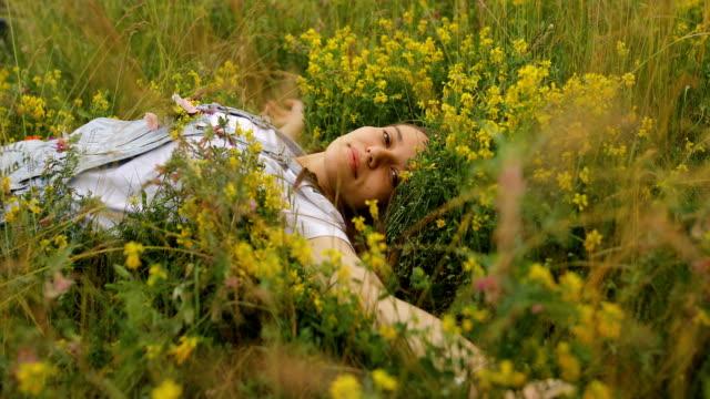 vidéos et rushes de jeune femme dormante avec des fleurs dans sa poche - yeux fermés