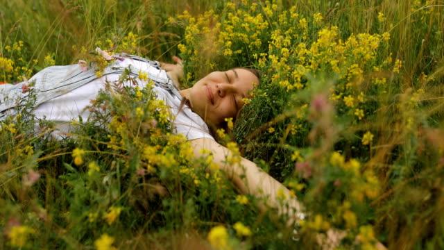 schlafende junge frau mit blumen in der tasche - augen geschlossen stock-videos und b-roll-filmmaterial
