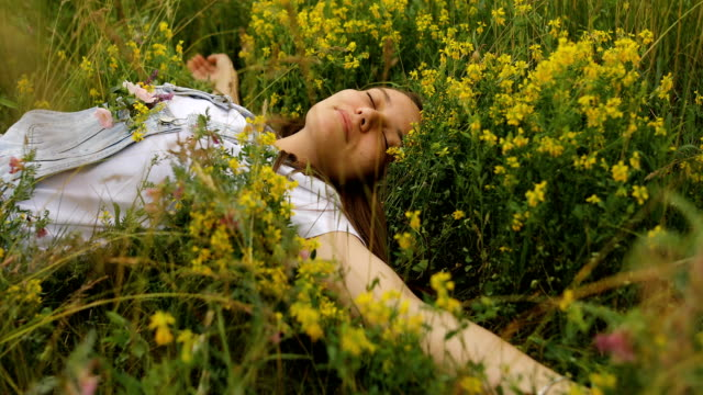 sleeping young woman with flowers in her pocket - sdraiato video stock e b–roll