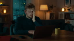 Sleepy and Exhausted Man Works on a Laptop while Sitting at His Desk at Home in the Middle of the Night.