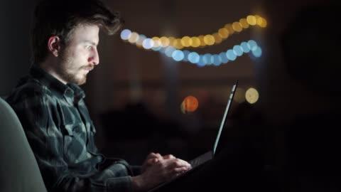 schlafender und müder mann arbeitet auf einem laptop, während er mitten in der nacht zu hause auf der couch sitzt. junge männliche studentin arbeitet spät am computer in der nacht. - männer stock-videos und b-roll-filmmaterial