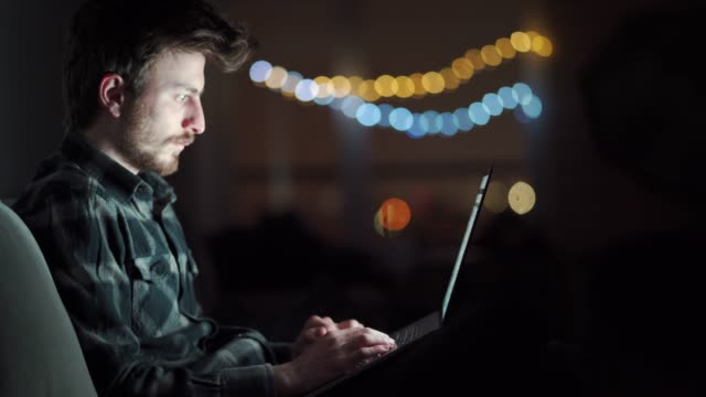 sleepy and tired man works on a laptop while sitting on couch at home in the middle of the night. young male student working late on a computer during the night. - image focus technique stock videos & royalty-free footage