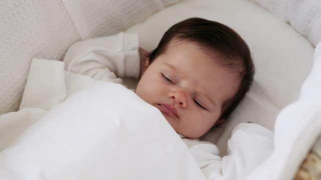 sleepy baby girl in bassinet - tutina video stock e b–roll