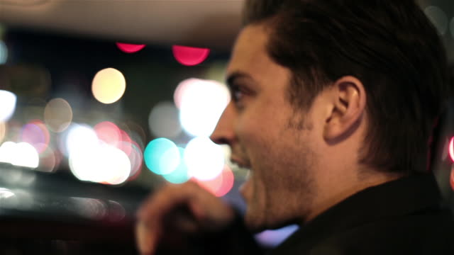 Sleepy guy talks and laughs in convertible on Las Vegas Strip late at night