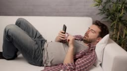 Sleepy man using smartphone on the couch