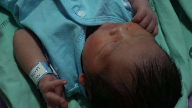 Sleepy newborn baby laying in hospital
