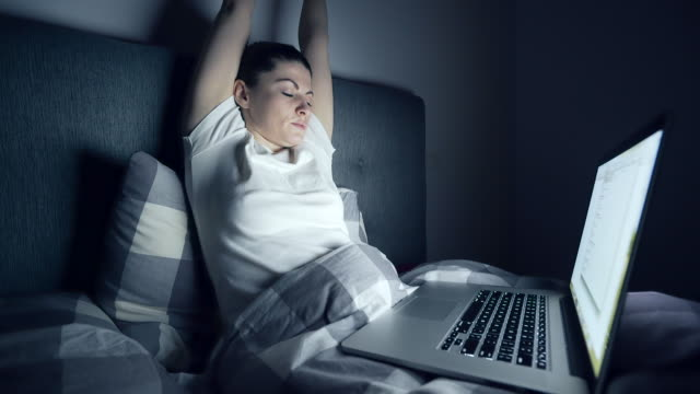 sleepy woman using a laptop late in night. - hands behind head stock videos and b-roll footage