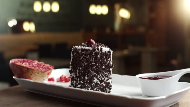 Slice of black forest cake with pomegranate and cherry topping on plate