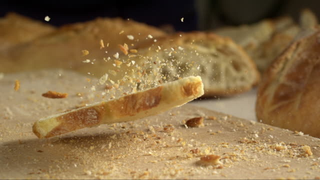 vídeos de stock, filmes e b-roll de slice of bread falling with crumbs in slow motion - faca faqueiro