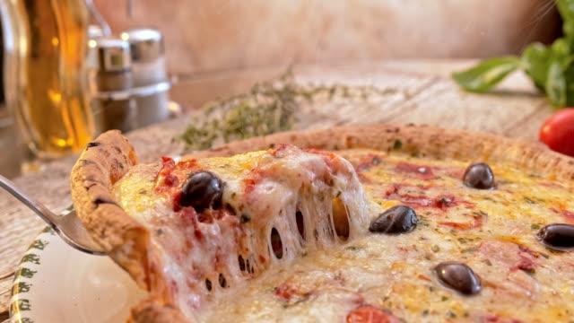 slo mo ds スライス チーズのピザ板から持ち上げられているの - 盛り付け点の映像素材/bロール