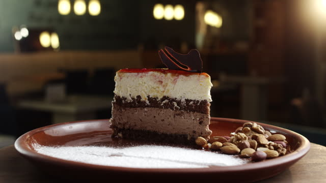 Slice of chocolate cake with cherry topping one plate with nuts, almonds and peanuts beside