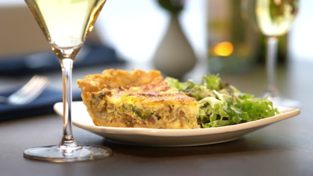 vidéos et rushes de slice of hearty quiche with fresh green salad, paired with white wine. - anorexie nerveuse