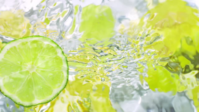 a slice of lime sliding in on surface of water from right and making splashes with out of focus submerged slices of lemon and lime on background - ライム点の映像素材/bロール