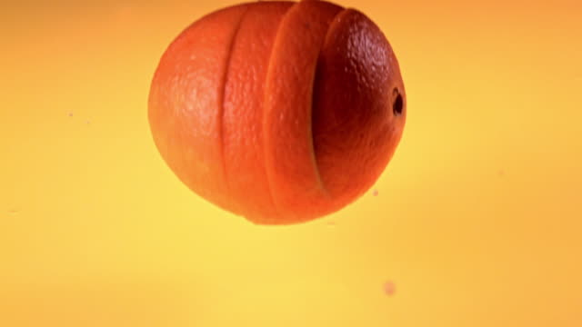 slice of orange falling into water - orange colour stock videos & royalty-free footage