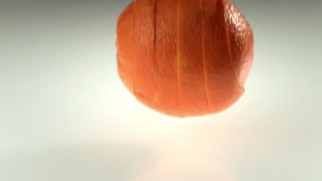 Slice of orange falling into water