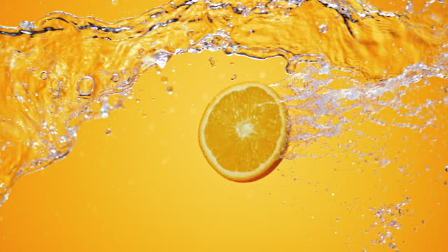 SLO MO Slice of orange in a water jet