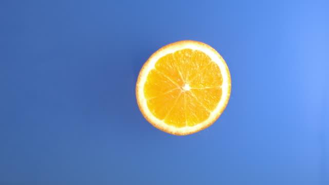stockvideo's en b-roll-footage met slice of orange is falling into blue water - tropische drankjes