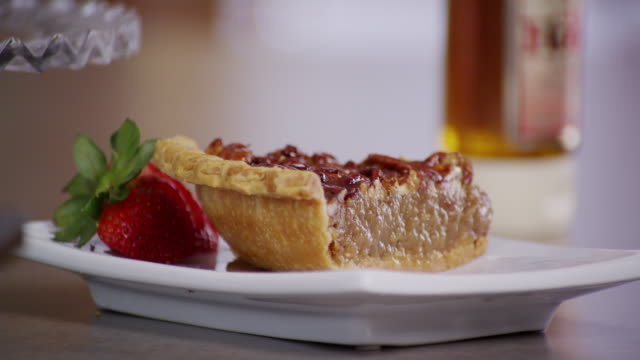 Slice of pecan pie on a white plate.