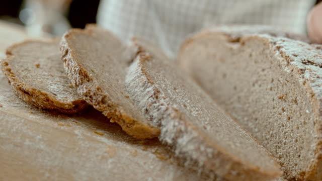vídeos de stock e filmes b-roll de slo mo ld a slice of rye bread falling to the side when being cut - pão