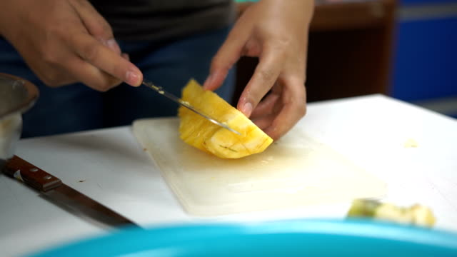 slice pineapple to small pieces on a white table - pineapple stock videos and b-roll footage