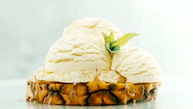 vídeos de stock e filmes b-roll de slice pineapple with ice cream on decorated with fresh mint on top - perto
