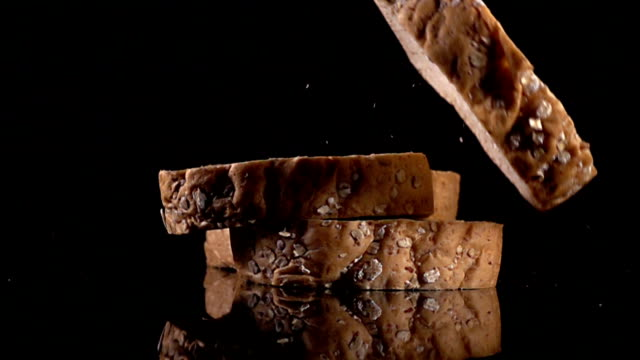 slice whole wheat bread drop on slow motion - bakery stock videos and b-roll footage