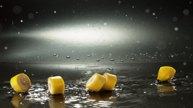 sliced banana falling down on wet surface and making ripples - slice of food stock videos & royalty-free footage