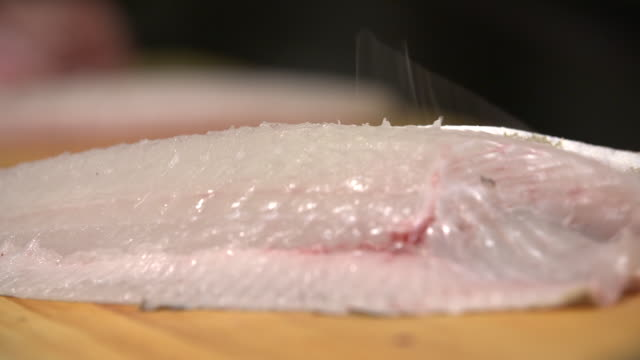 vídeos de stock, filmes e b-roll de sliced fish being piled on a cutting board - sashimi