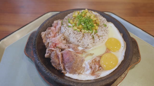 sliced wagyu beef steak on topped rice bowl with egg on hot pan. - donburi stock videos and b-roll footage