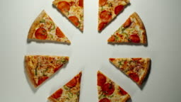 Slices Of Big Pizza Is Eaten Up On A White Surface in Different Directions