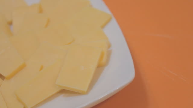 Slices of cheddar cheese on a square white plate on a blue surface, from top view.