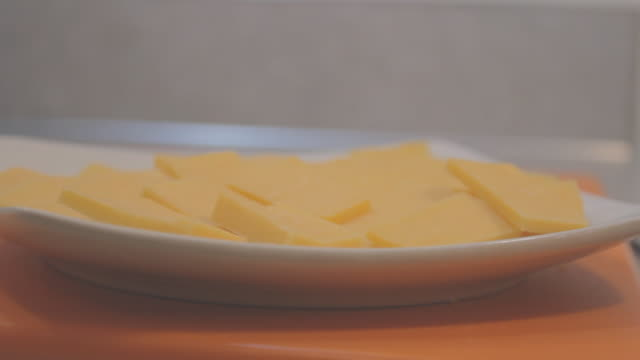 Slices of cheddar cheese on a square white plate on a blue surface, raised side view.