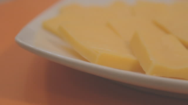 Slices of cheddar cheese on a square white plate on an orange surface, from side view.