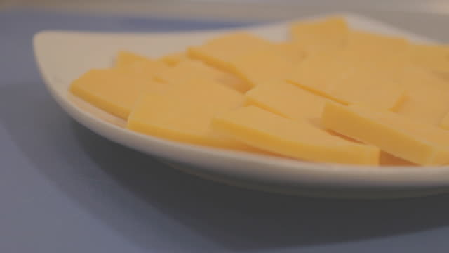 Slices of cheddar cheese on a square white plate on an orange surface, from top view.