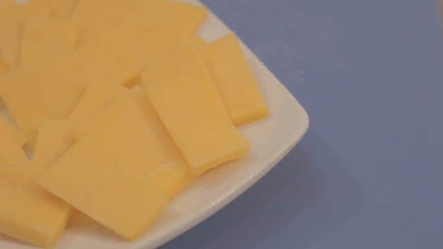 Slices of cheddar cheese on a square white plate on an orange surface, raised side view.
