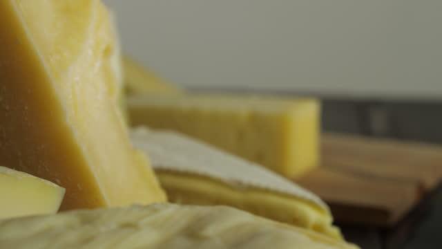 vídeos de stock, filmes e b-roll de fatias de queijo na mesa, queijos de vários tipos giram em câmera lenta, brie, parmigiano, caciotta, queijo suíço - cheese