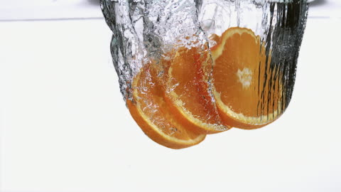 ms slo mo slices of orange entering into water against white background / vieux pont, normandy, france  - orange stock videos & royalty-free footage