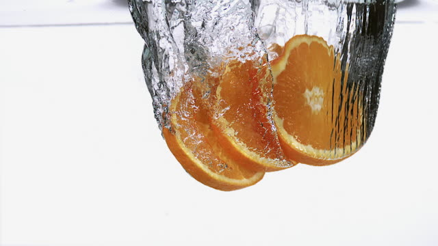 MS SLO MO Slices of orange entering into water against white background / Vieux Pont, Normandy, France