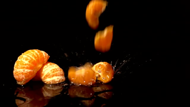 slices of peeled oranges falling on black background - tangerine stock videos and b-roll footage
