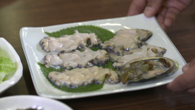 Slices of raw abalone on the plate (Korean food)