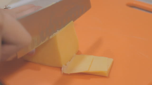 Slicing a block of cheddar cheese on an orange cutting board.