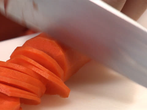 slicing a carrot on a white board - unknown gender stock videos & royalty-free footage