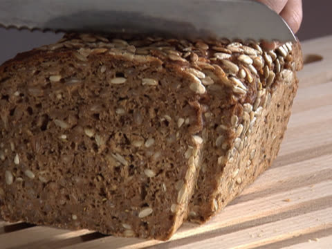 slicing a loaf of sunflower seed bread - unknown gender stock videos & royalty-free footage