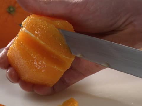 vídeos y material grabado en eventos de stock de slicing and removing segments from a peeled orange - unknown gender