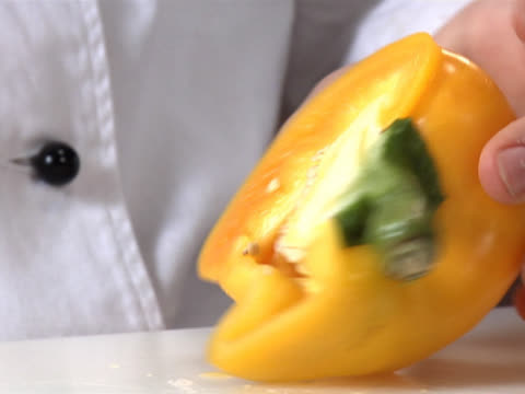 slicing and removing the stem and seed from a yellow bell pepper - unknown gender stock videos & royalty-free footage