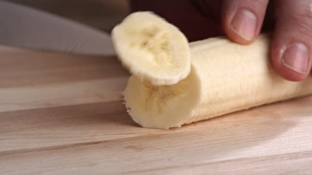vídeos de stock e filmes b-roll de slicing banana on wooden cutting board pancake recipe - fatia