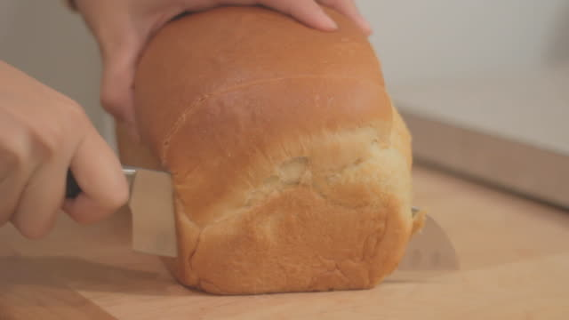 vídeos de stock e filmes b-roll de slicing bread on wooden cutting board. - fatia