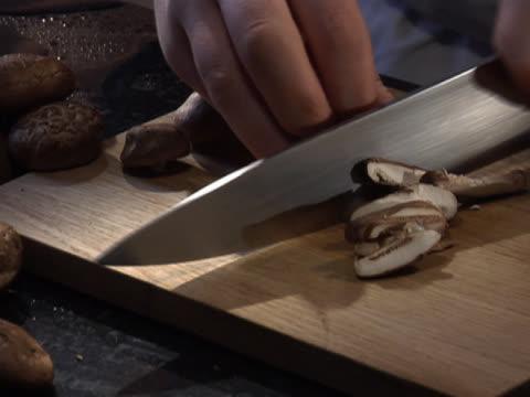 vídeos y material grabado en eventos de stock de slicing brown mushrooms - unknown gender