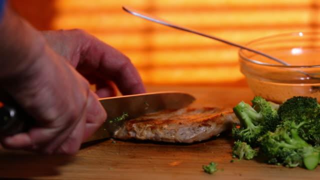 Slicing grilled pork fillet.