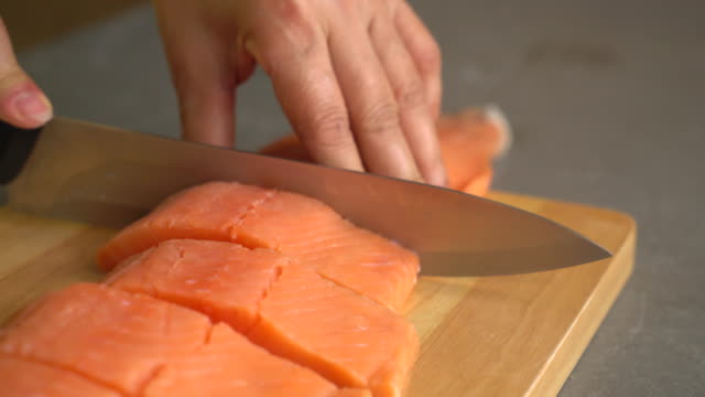slicing salmon on wood board